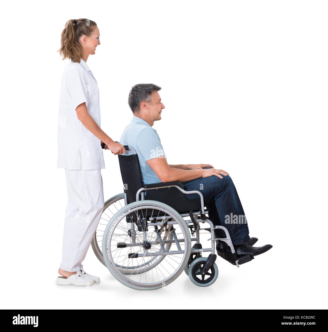 A Female Caretaker Pushing Disabled Male Patient On Wheelchair Against White Background - Stock Image