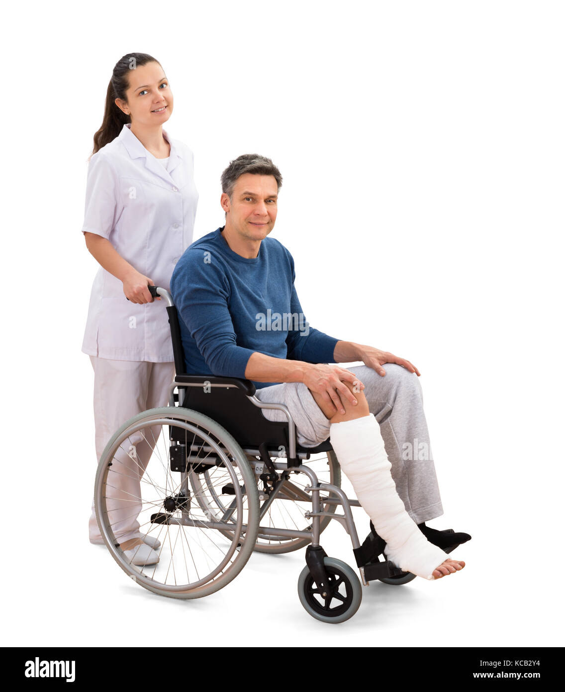 Portrait Of A Young Female Nurse With Disabled Male Patient On Wheelchair - Stock Image