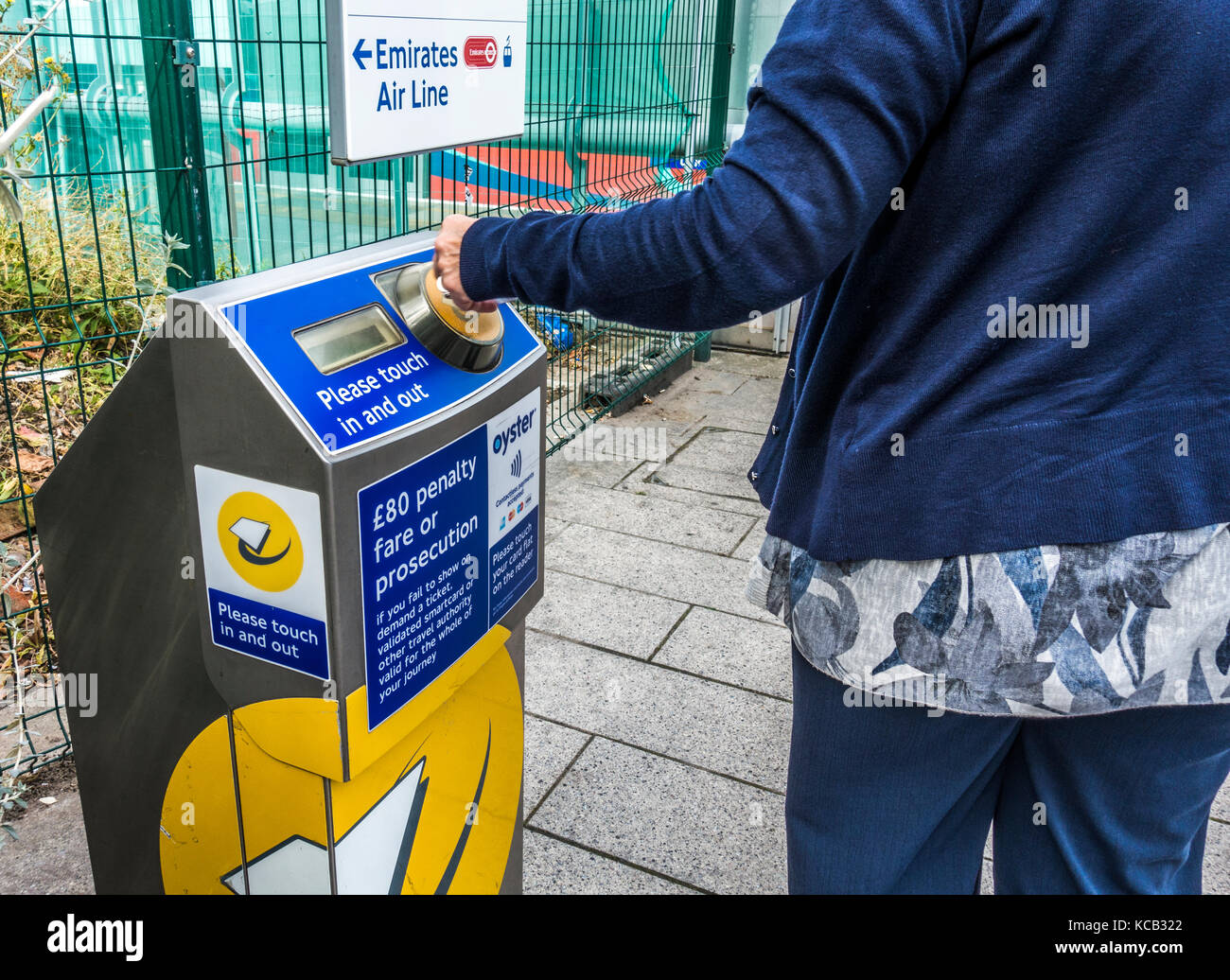 A woman commuter tapping her bank card on a contactless payment machine for the Docklands Light Railway (DLR) in - Stock Image