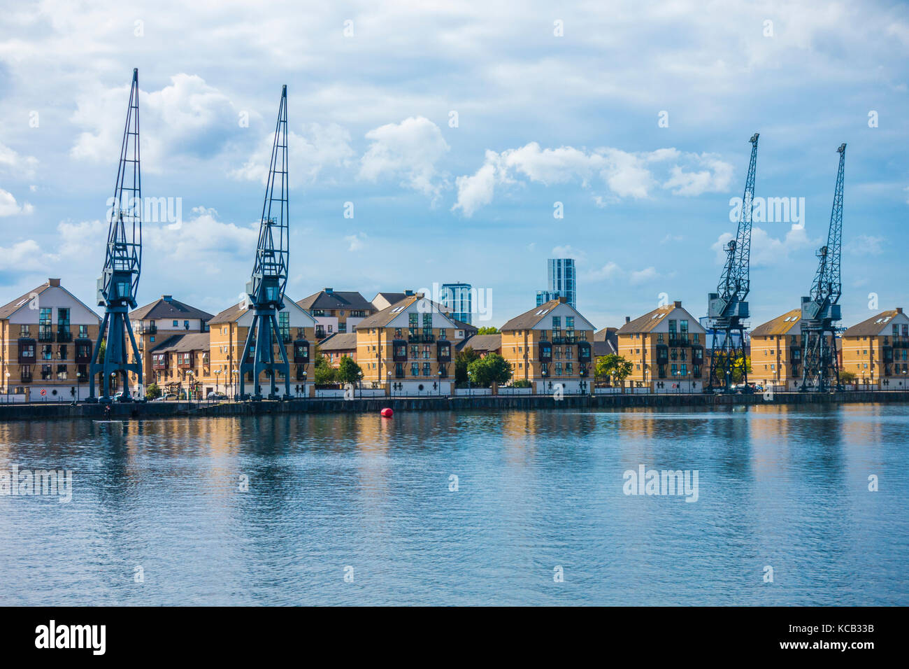 Modern mews houses and Grade II listed old cranes overlooking Royal Victoria Dock on the Greenwich side, in East - Stock Image