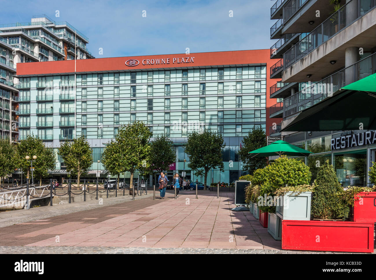Crowne Plaza hotel, paved area and surrounding buildings, with people walking nearby, Royal Victoria Dock, Docklands, - Stock Image