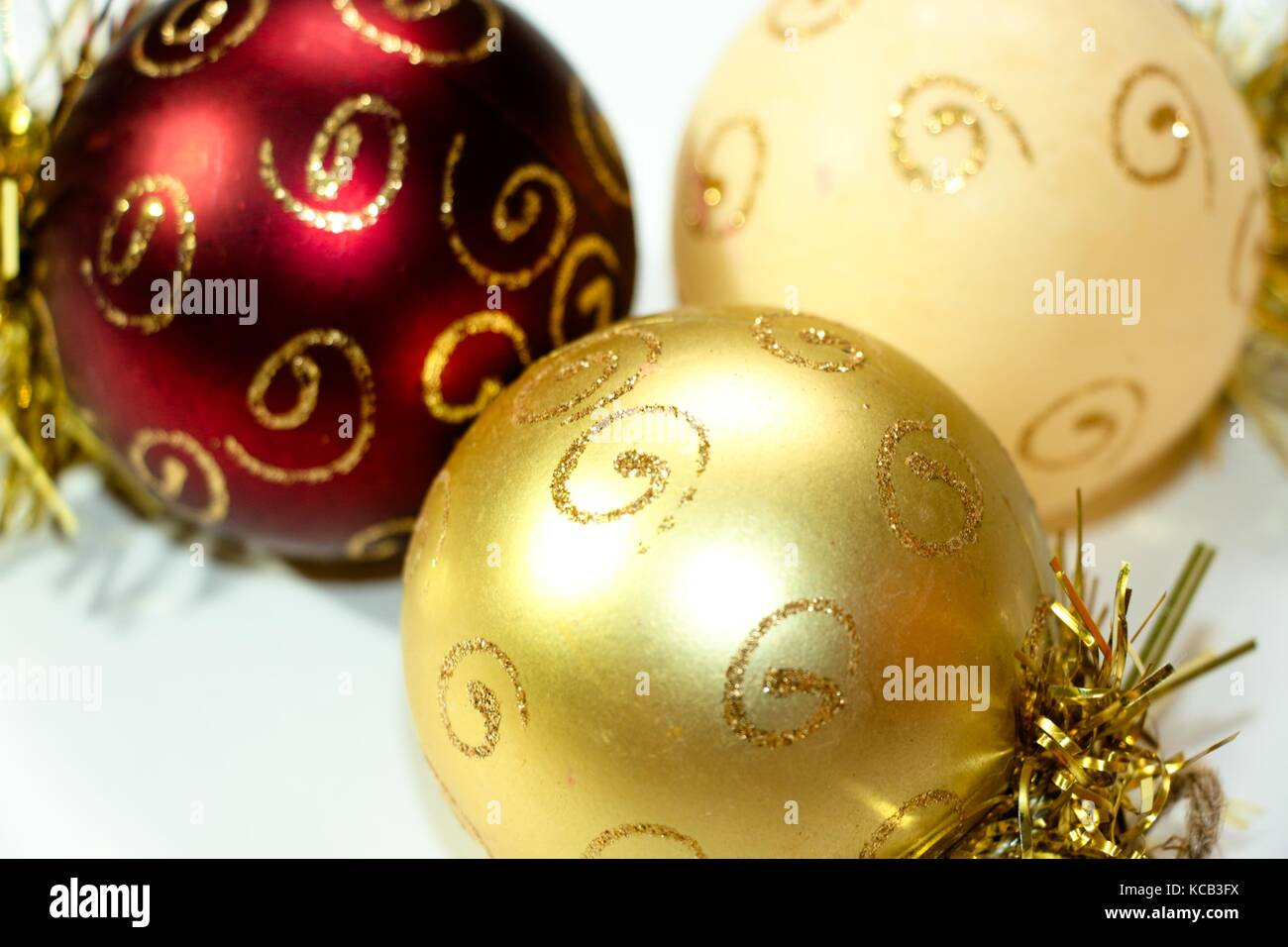 Three multi-colored Christmas decorations in the shape of a balloon, painted with gold patterns. A composition of - Stock Image