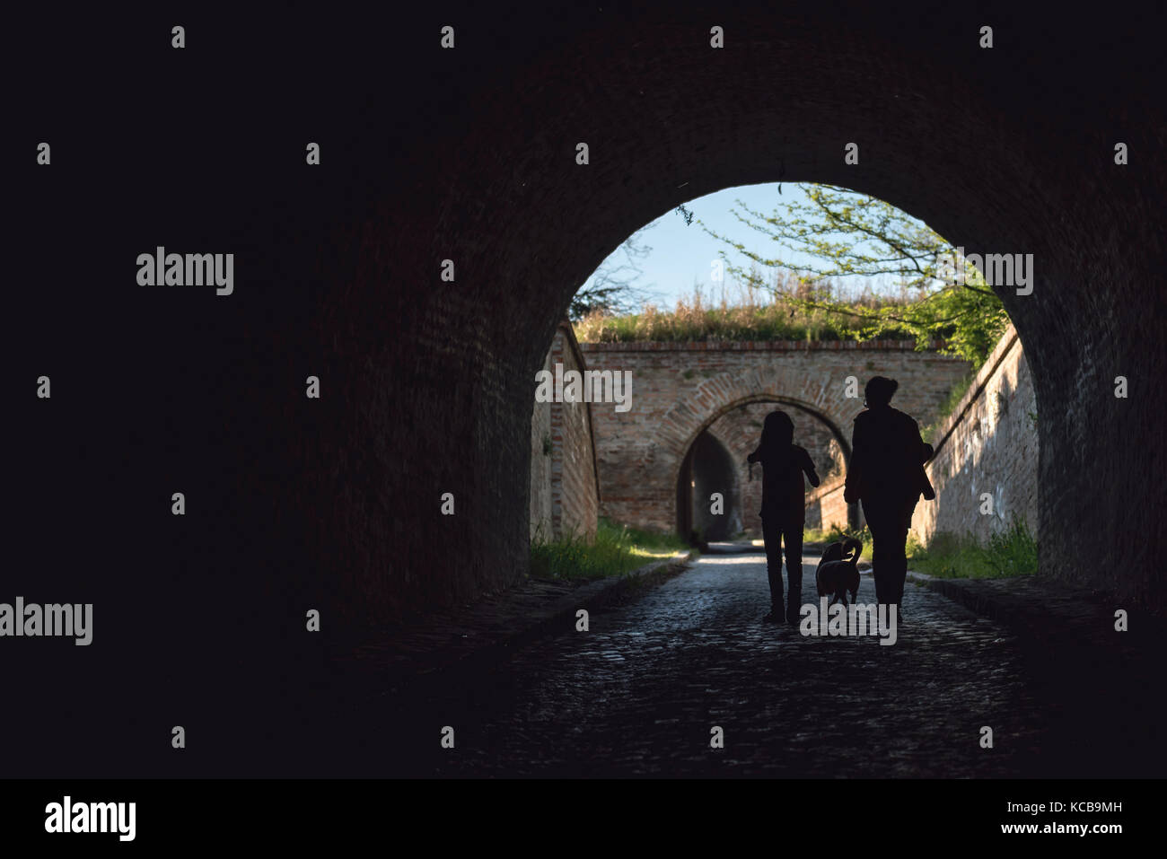 Mother and daughter walking in a tunnel with a dog - Stock Image