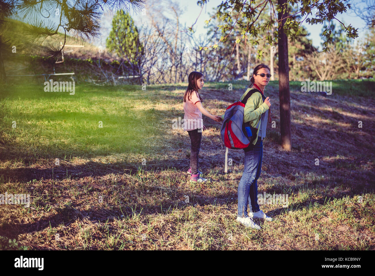 Mother wearing backpack and daughter hiking outdoors - Stock Image