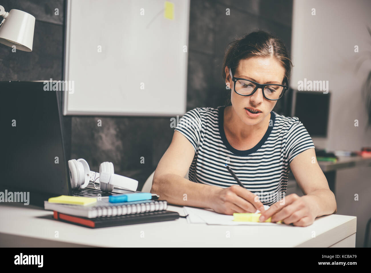 Woman wearing eyeglasses working late at the office and writing - Stock Image
