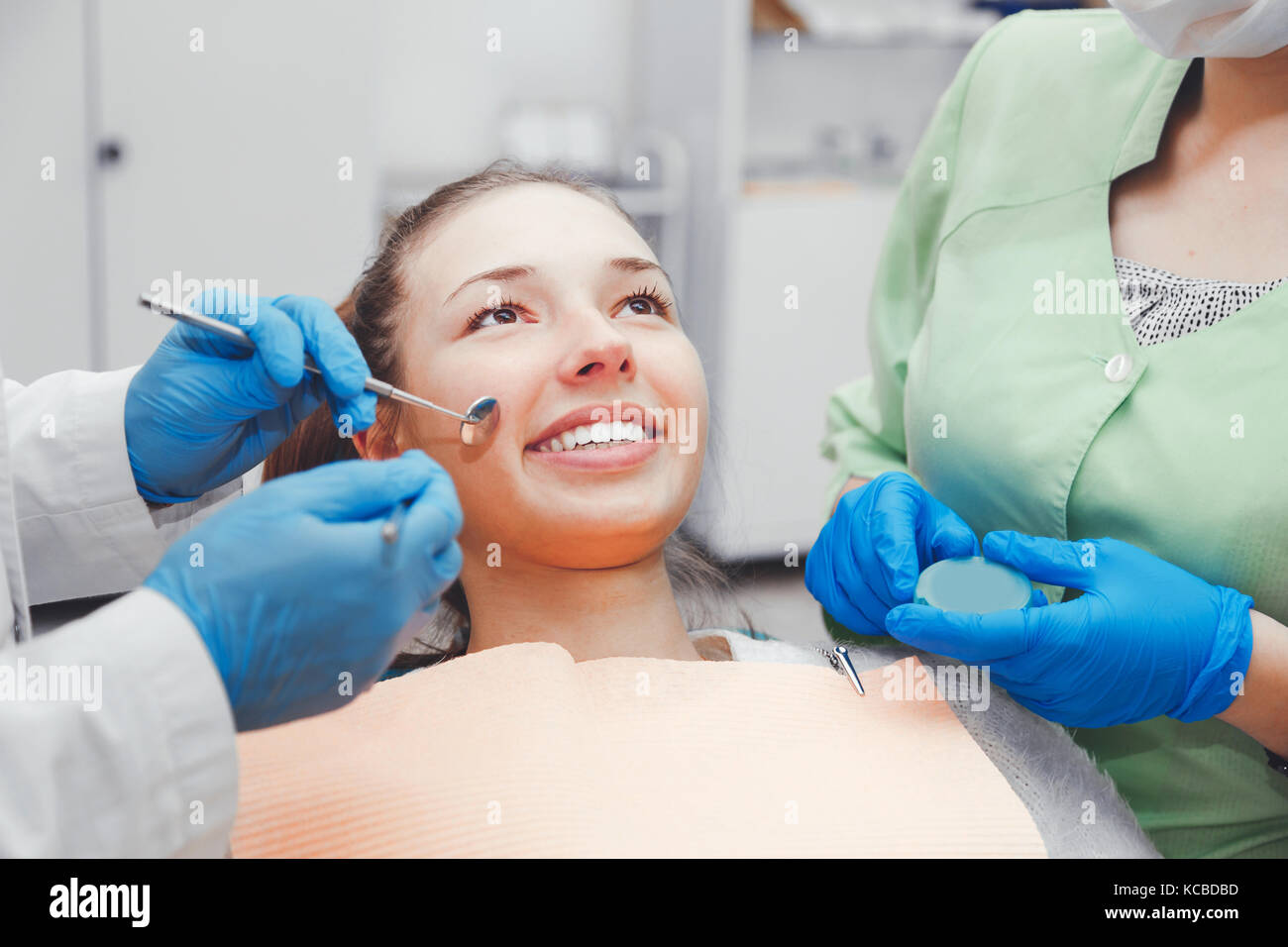 The girl with a beautiful smile at the reception at the dentist. - Stock Image