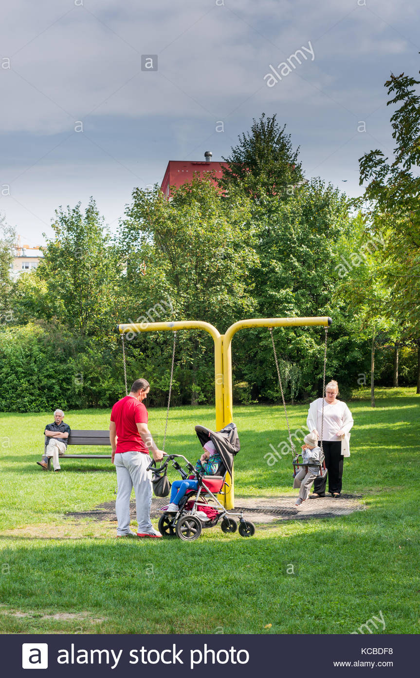 Man and woman with two children including one disabled in a buggy by a swing set on a playground on September 2017 - Stock Image