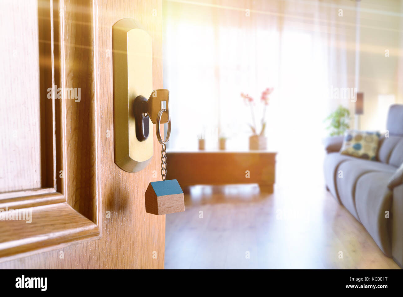 Open entrance door detail of a house with keys in the lock and furnished living room in the background with golden - Stock Image