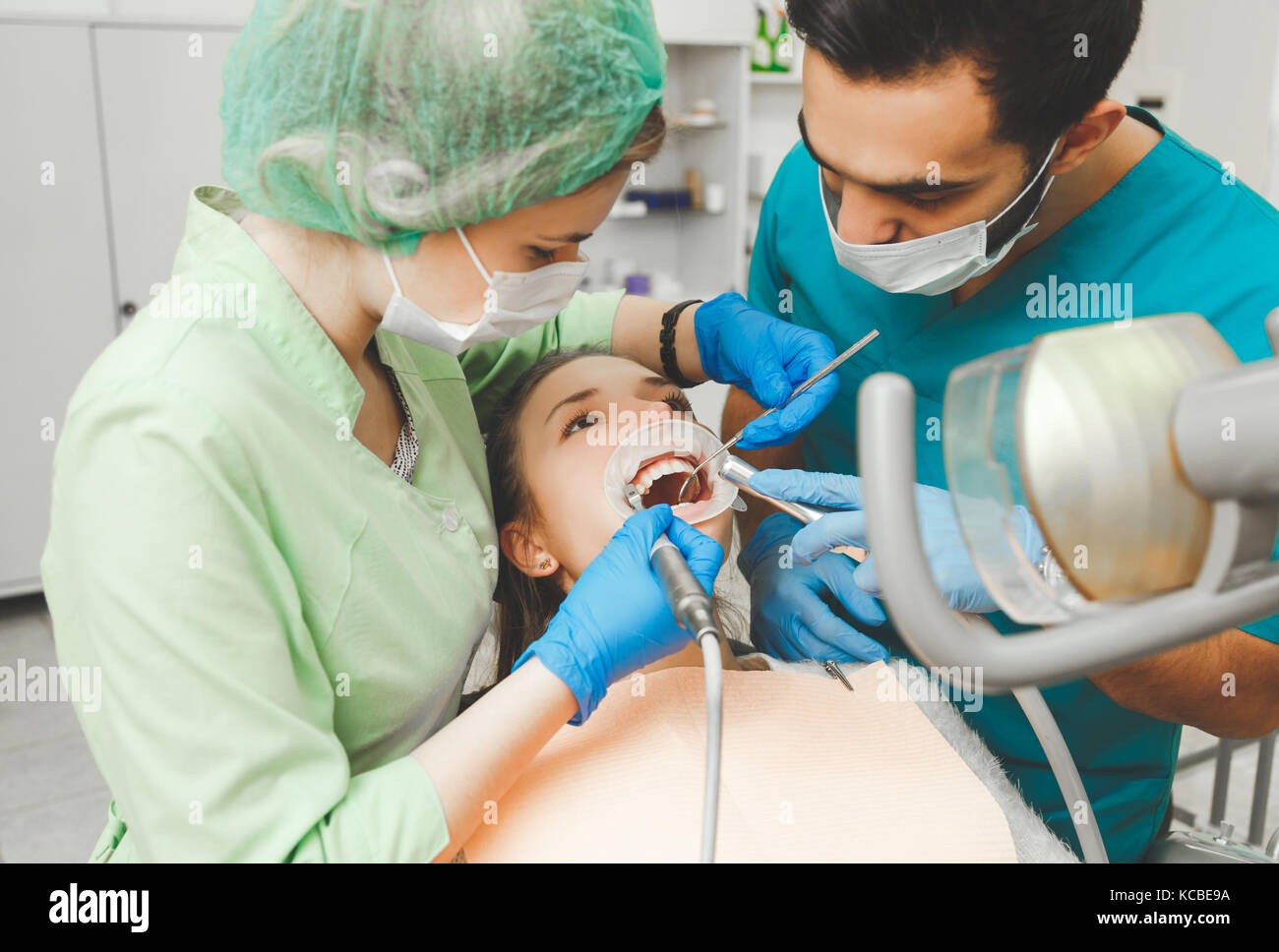 Beautiful girl on preventive teeth cleaning at the intern dentist. - Stock Image