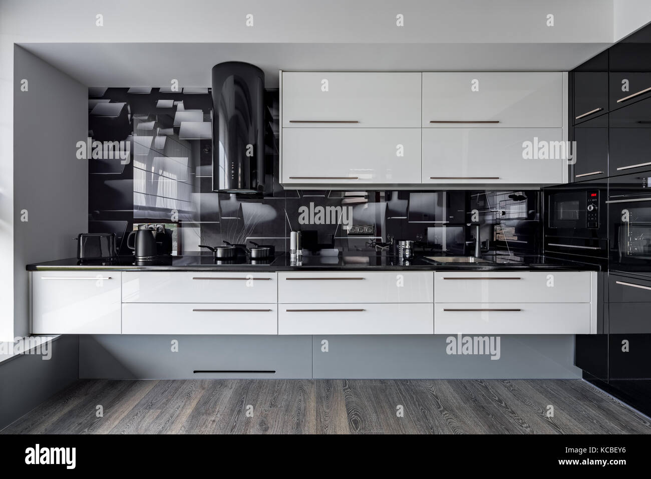 Modern Kitchen With White Cupboards And Black Wall Tiles