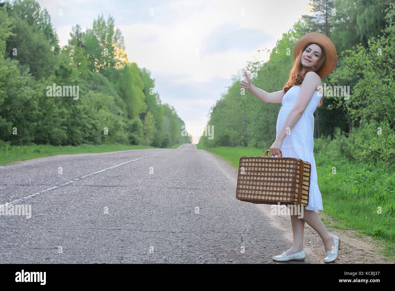 girl in a white sundress and wicker suitcase walking on rails - Stock Image