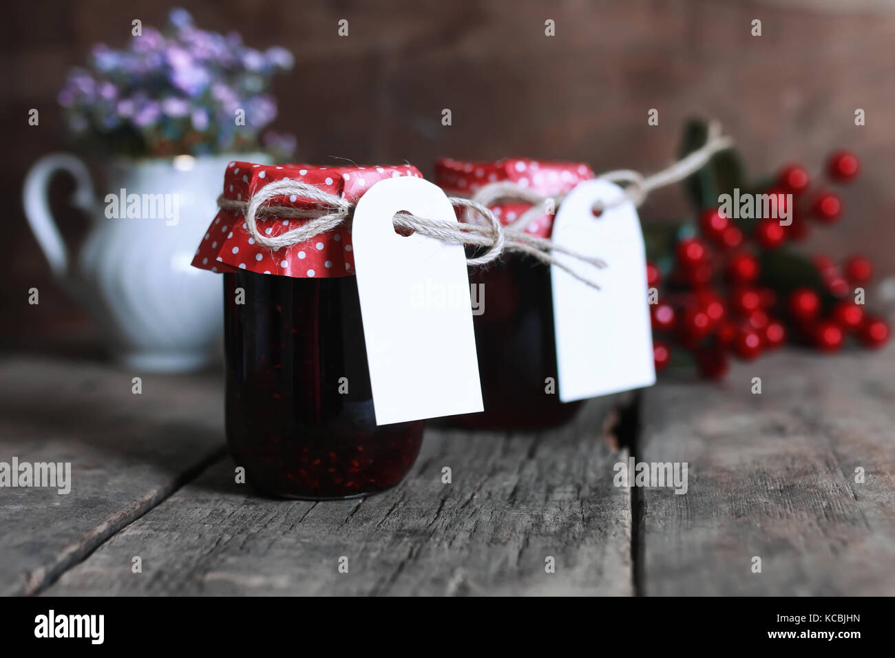 rustic homemade jam jar wooden background and flower - Stock Image