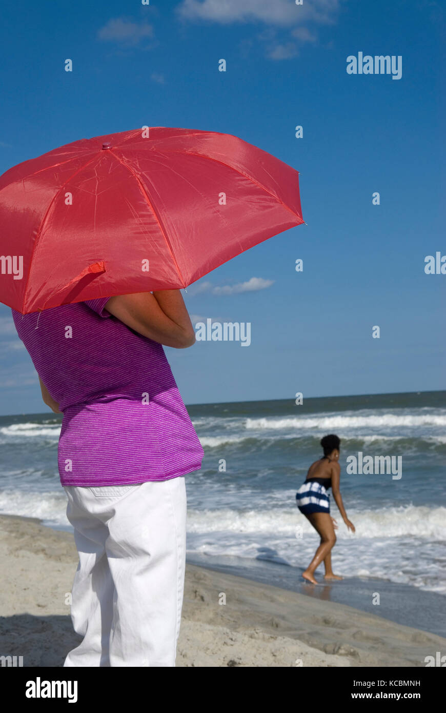 Woman holding red umbrella while viewing the ocean Myrtle Beach SC, USA. Stock Photo