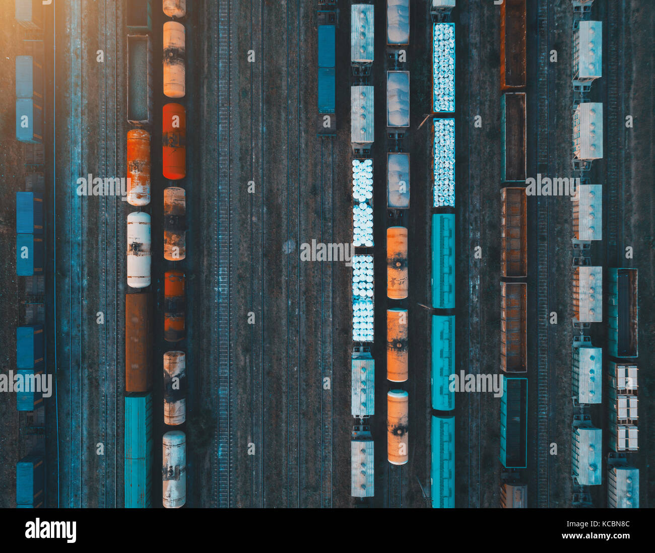 Aerial view of colorful freight trains on the railway station. Cargo trains close-up. Wagons with goods on railroad. - Stock Image