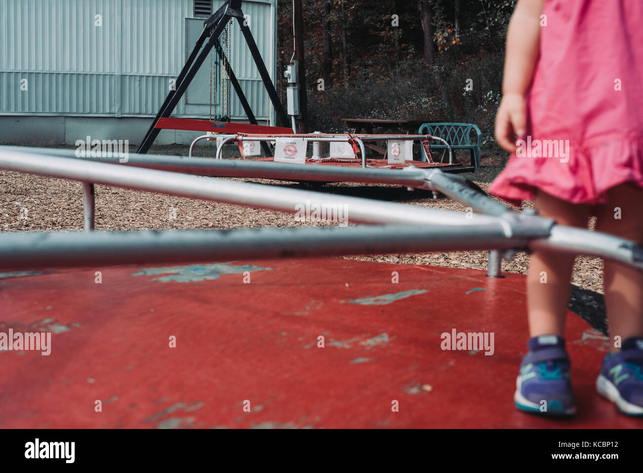 A toddler stands on a merry go round on a low income playground - Stock Image