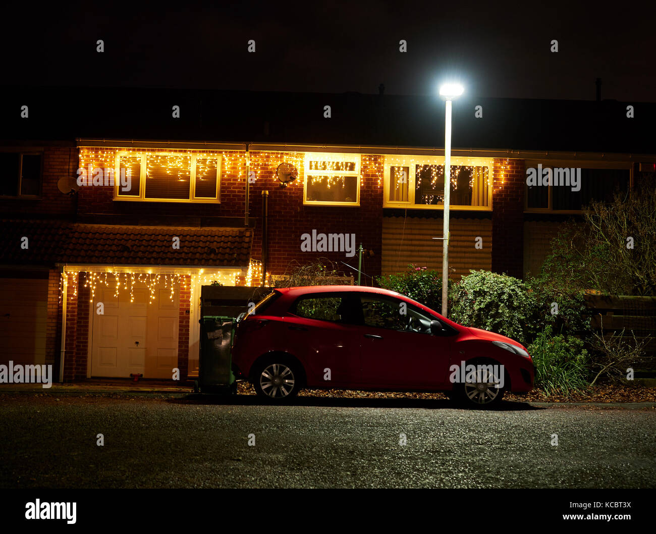 A car sat under the security of a street lamp with christmas lights a car sat under the security of a street lamp with christmas lights on the house behind it aloadofball Image collections