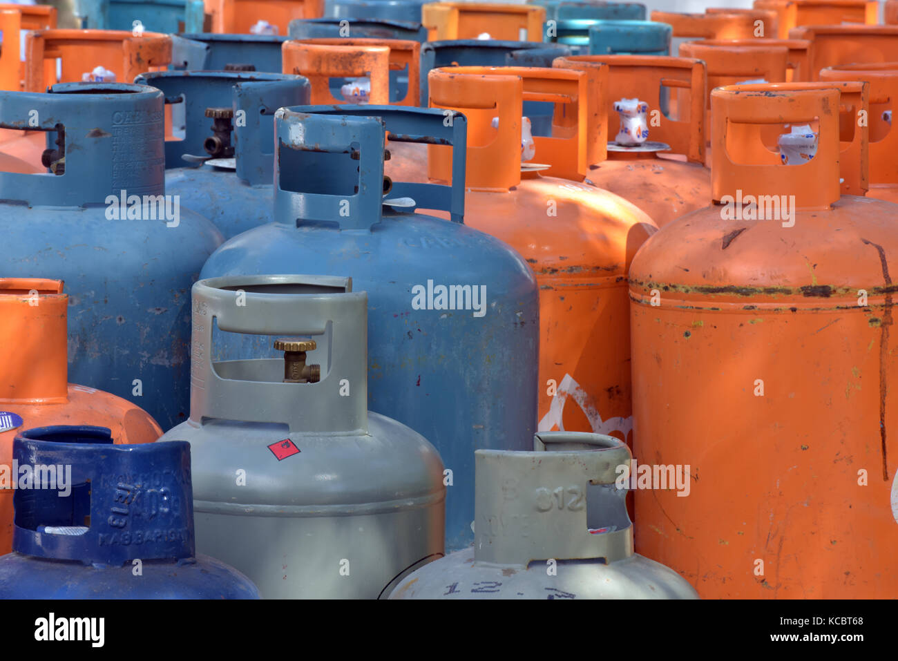 Camping gas bottles on the back of a lorry lined or stacked in patterns and painted blue and orange. Butane gas - Stock Image