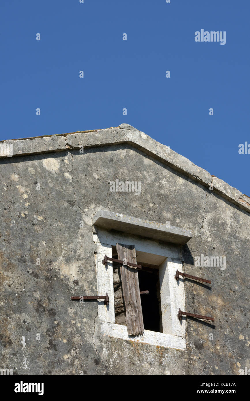 a typically greek building with broken wooden shutters and hinges against a clear blue sky. - Stock Image