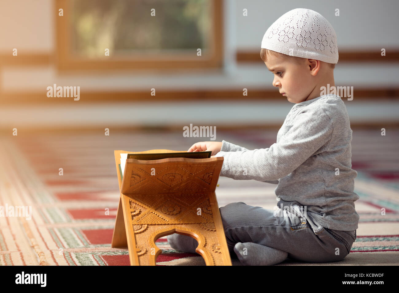 The Muslim child prays in the mosque, the little boy prays to God, Peace and love in the holy month of Ramadan. - Stock Image