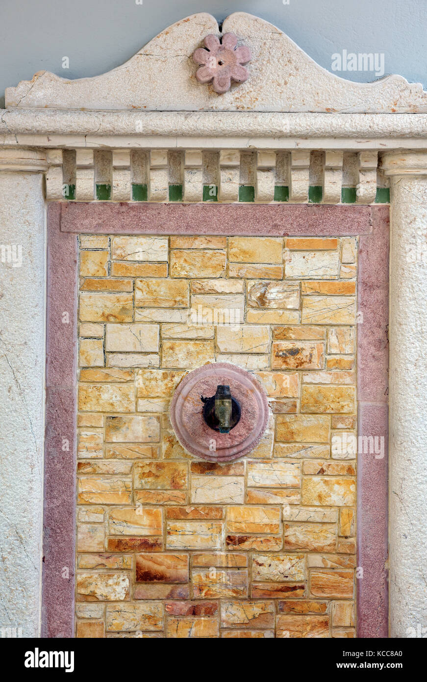 a water fountain or font for drinking set into an ornate surround on a stone wall with a broken pediment above. - Stock Image