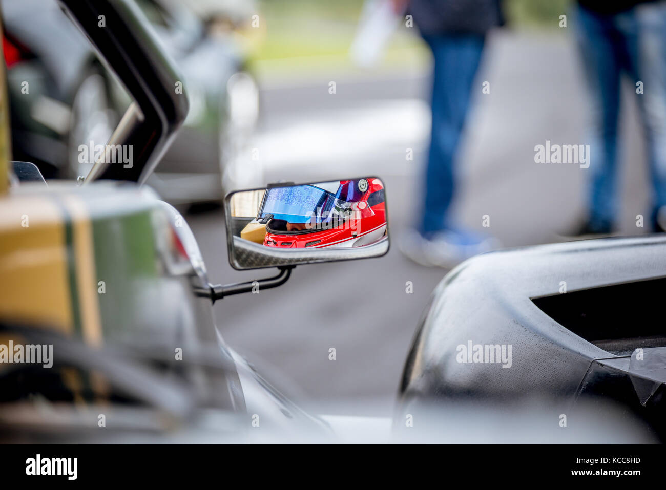 Motor sport car driver detail on rear view mirror before race start on starting grid - Stock Image