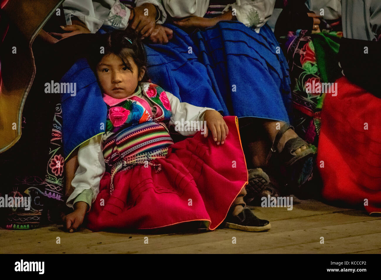 Cute Peruvian girl sat in traditional dress - Stock Image