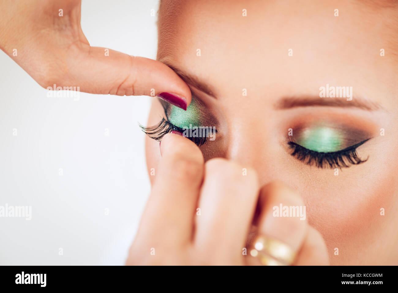 e9ce6611b87 Close up of a makeup artist applying the false eyelashes to model ...