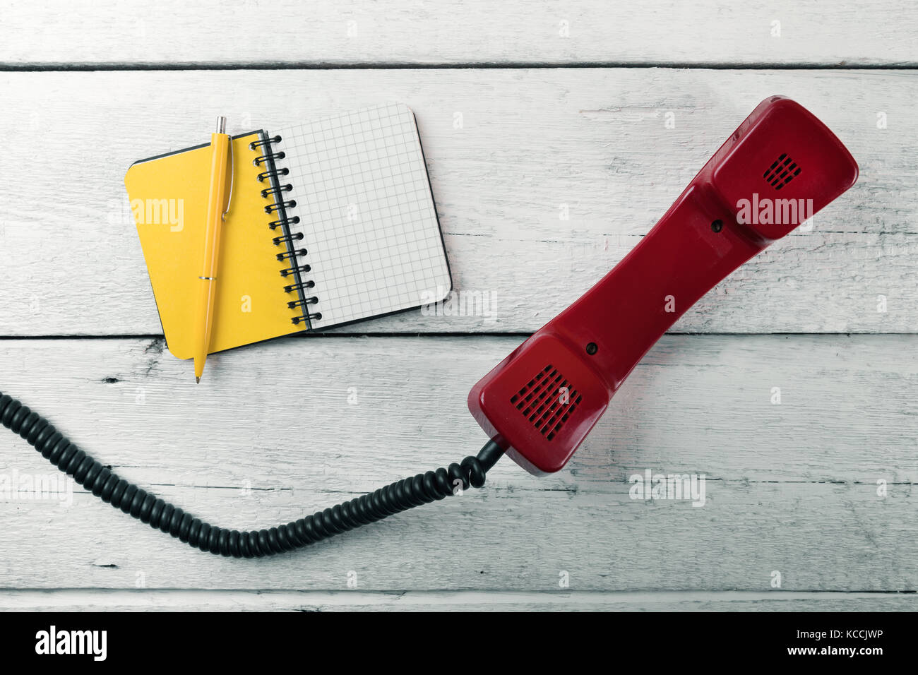 phone handset and blank notebook on white wood table - Stock Image
