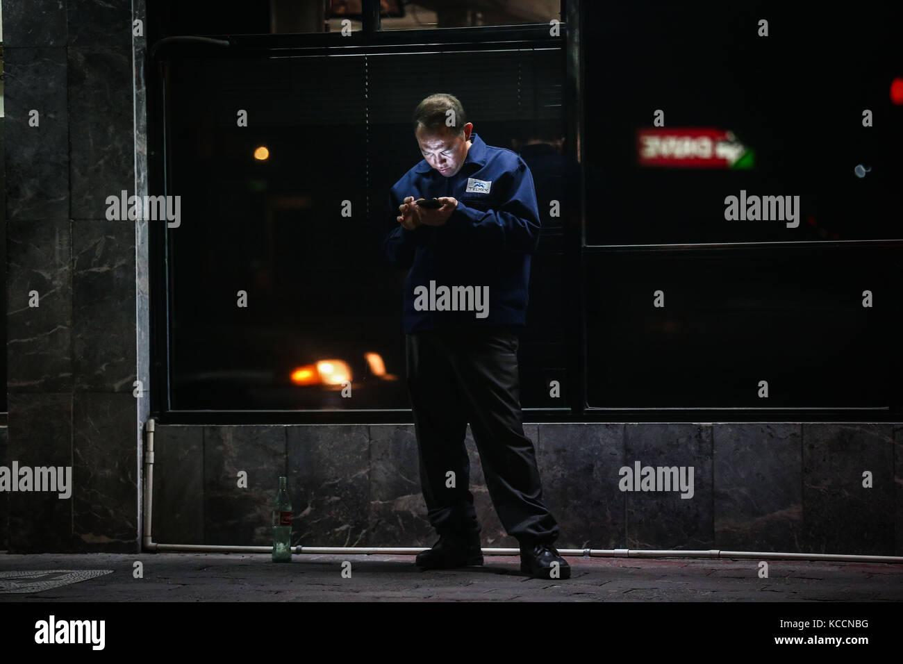 Una persona se detiene al otro lado de la acera de un negocio de cafe para tomar la señal de wifi en su celular. - Stock Image