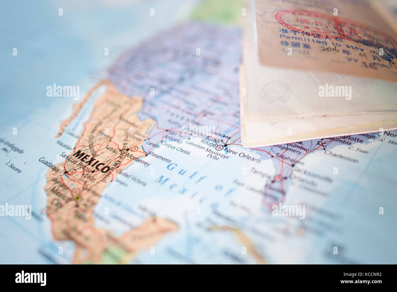 selective focus a blurred passport with entry stamps is on a geographical map of the world the map shows the united states an mexico