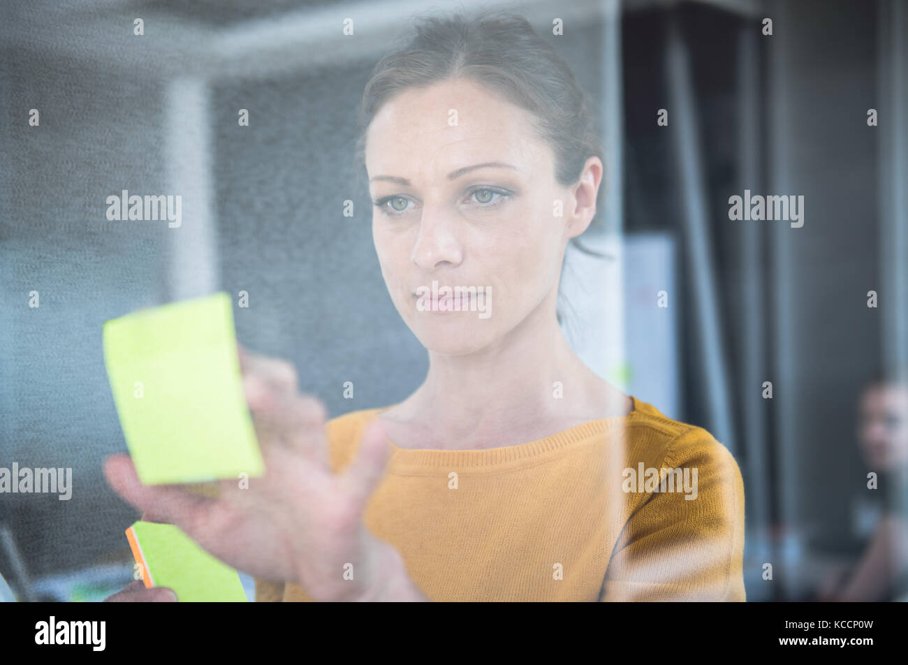 Woman writing notes on the glass board at the office - Stock Image