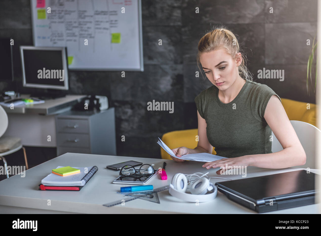 Young business woman doing paperwork in the office - Stock Image