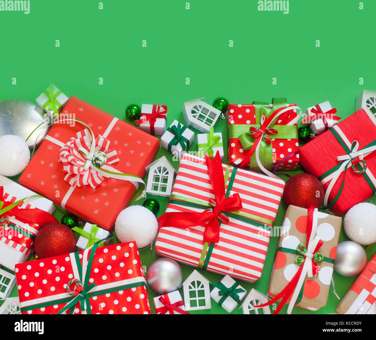 Christmas presents in red packaging. Satin colored ribbons. Green background. - Stock Image