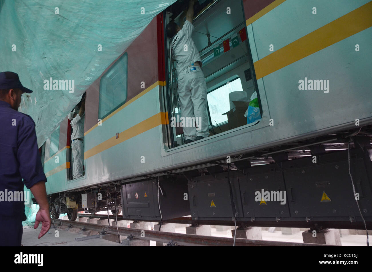 Chinese engineers busy in work on Orange Line Metro Train at