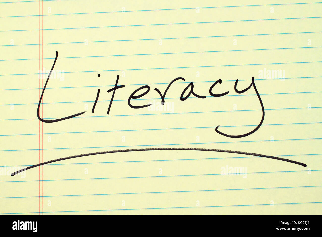 The word 'Literacy' underlined on a yellow legal pad - Stock Image