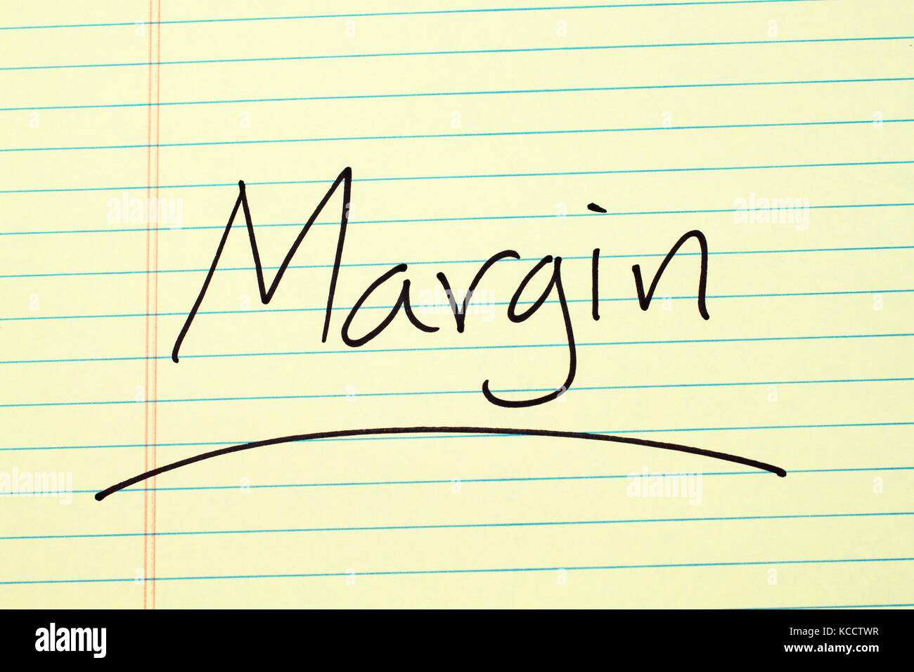 The word 'Margin' underlined on a yellow legal pad - Stock Image