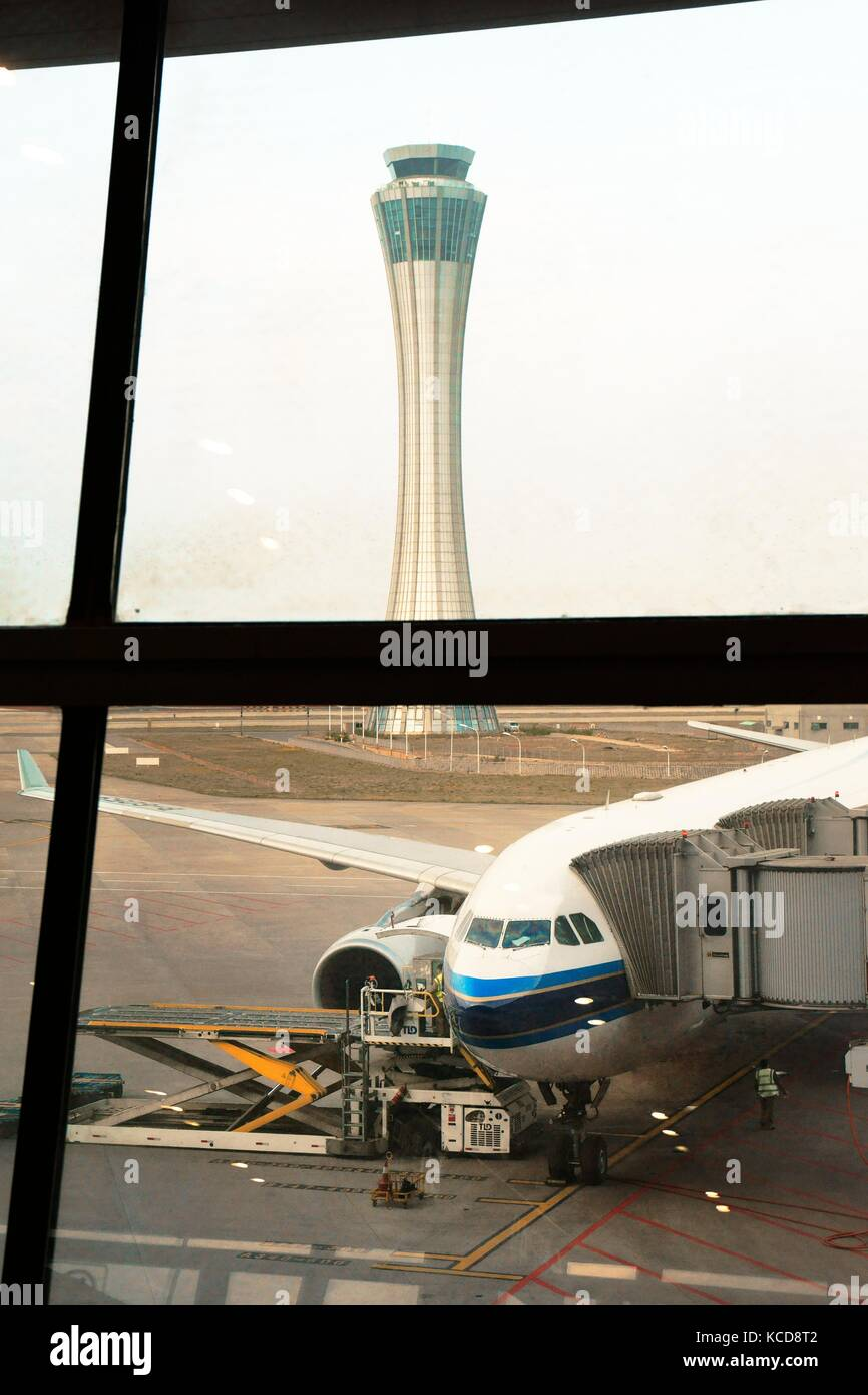 Kunming Changshui International Airport, Yunnan, China. Control tower and passenger airplane on apron preparing - Stock Image