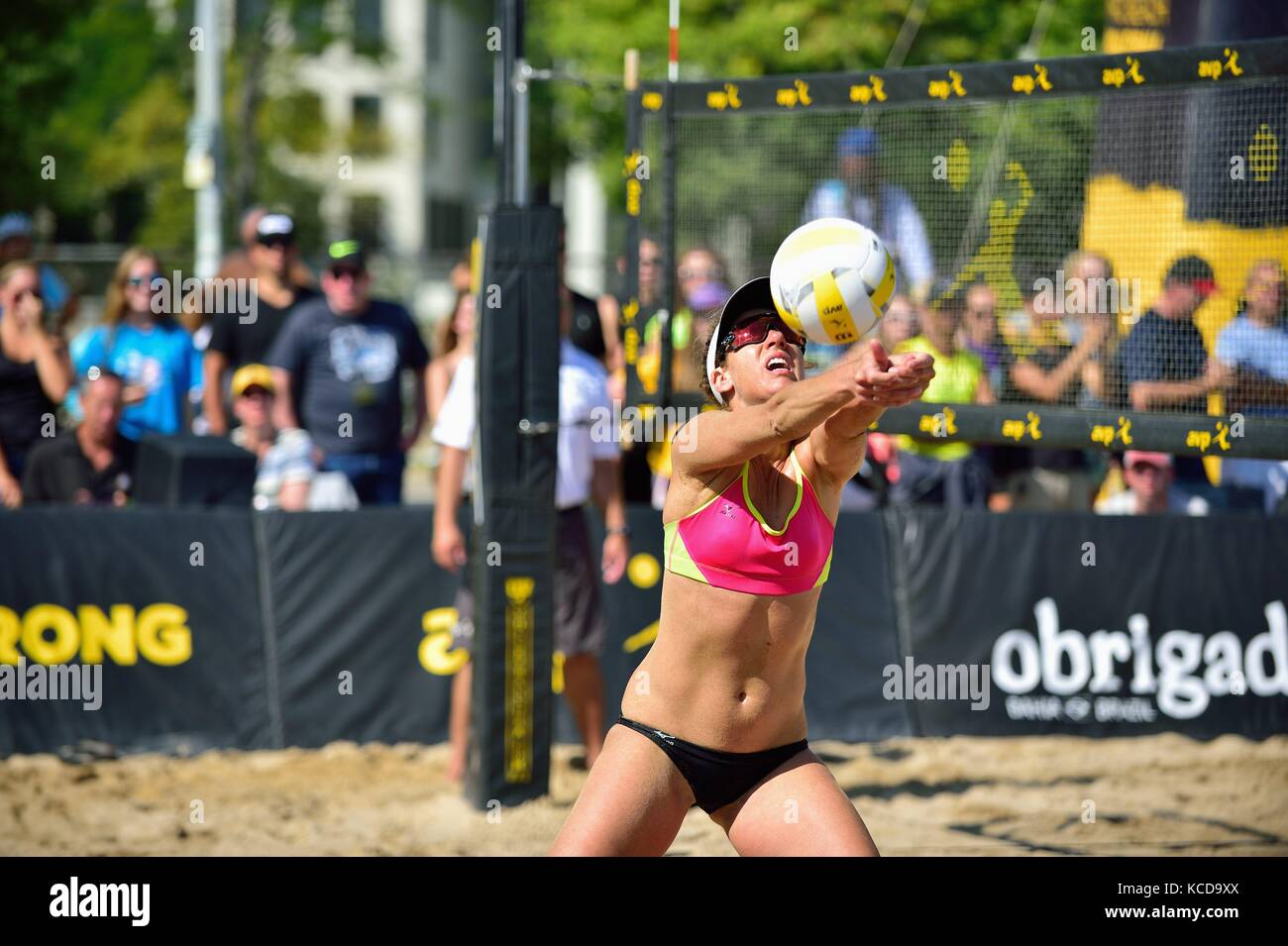 April Ross after had just rebounding from a dive to the sand to perform this set for a kill shot from her partner. - Stock Image