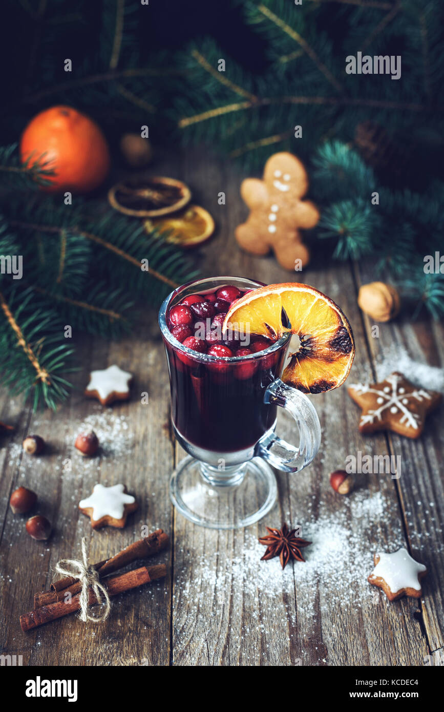 Mulled wine in glass with cranberries and spices decorated with burnt orange. Christmas drink. Holiday food concept - Stock Image