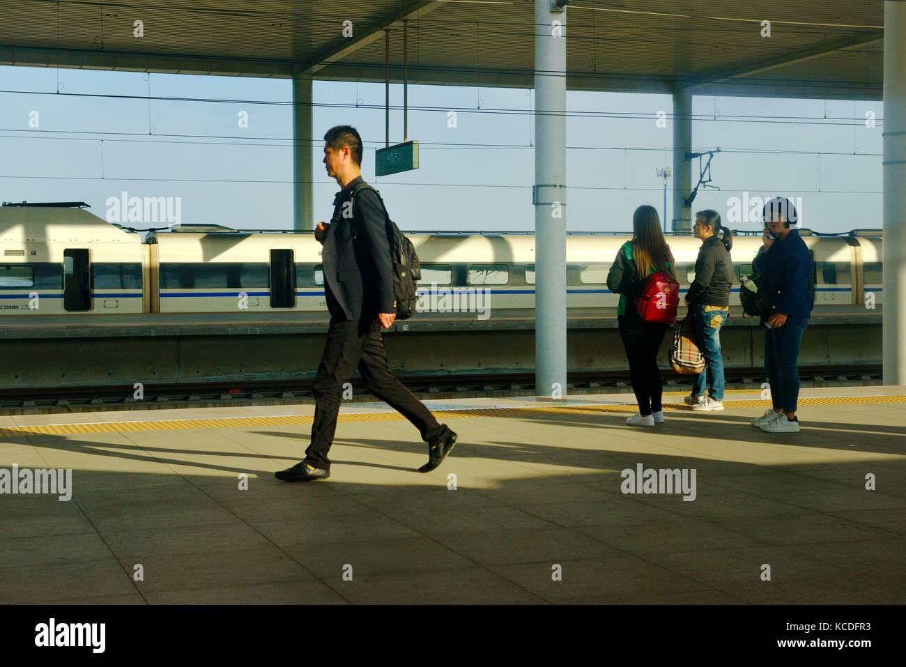 Platform, rail train and passengers on new Chinese railway station at Baoding on the Beijing Shijiazhuang high speed - Stock Image