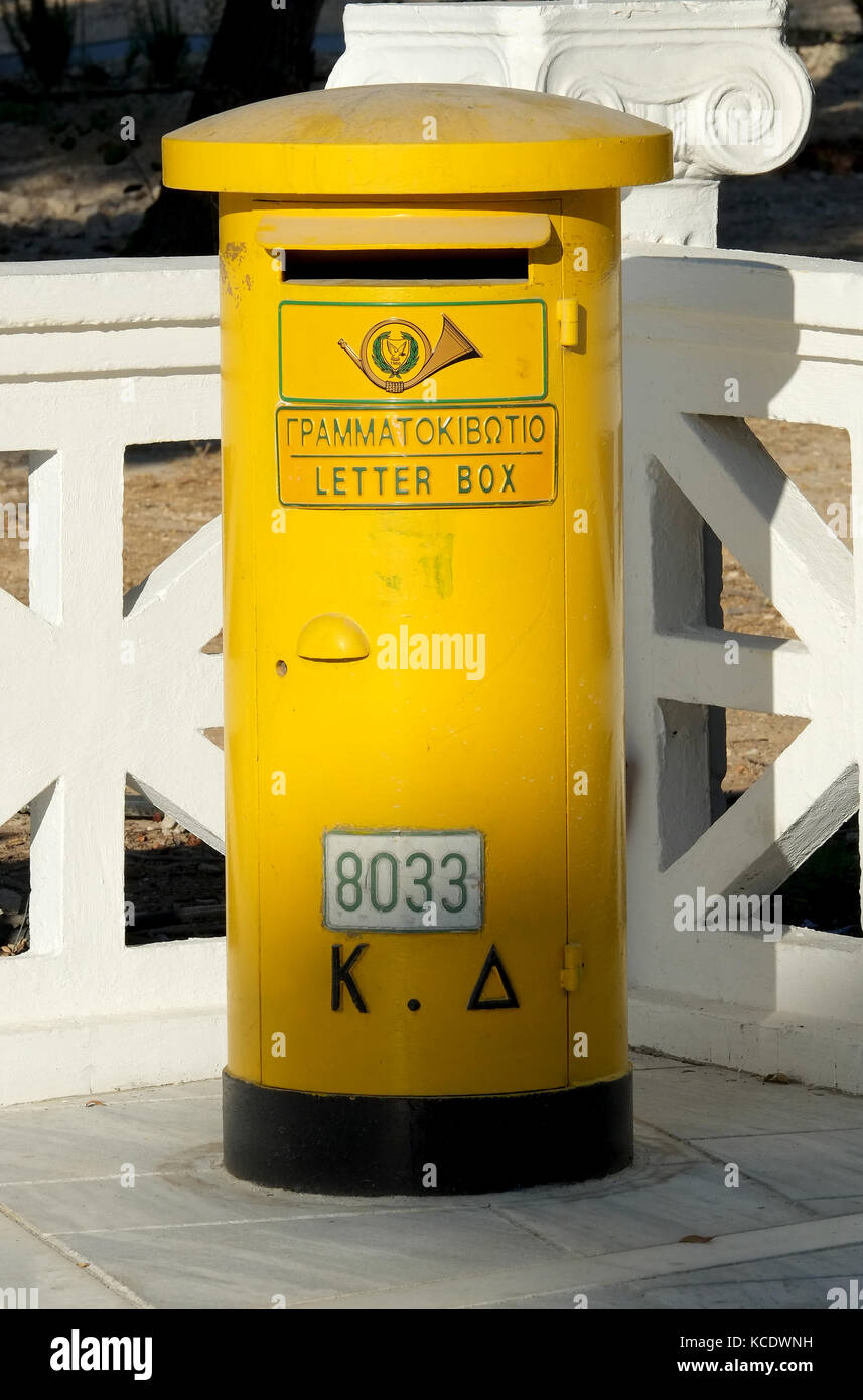 A yellow letter box in Paphos old town, Cyprus. - Stock Image