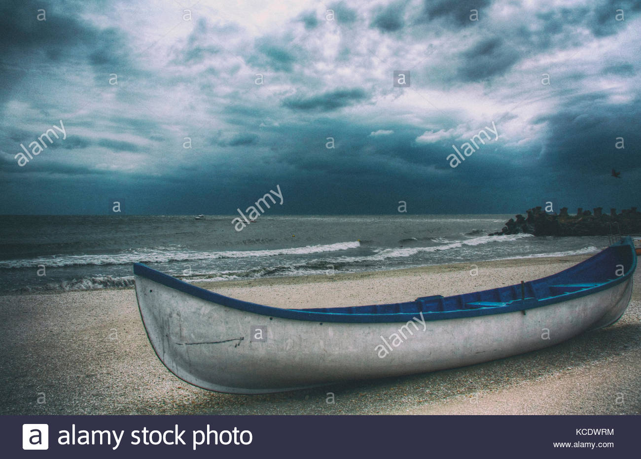A blue and white rowing boat on the beach next to the sea. The sky is dark and covered in clouds - Stock Image