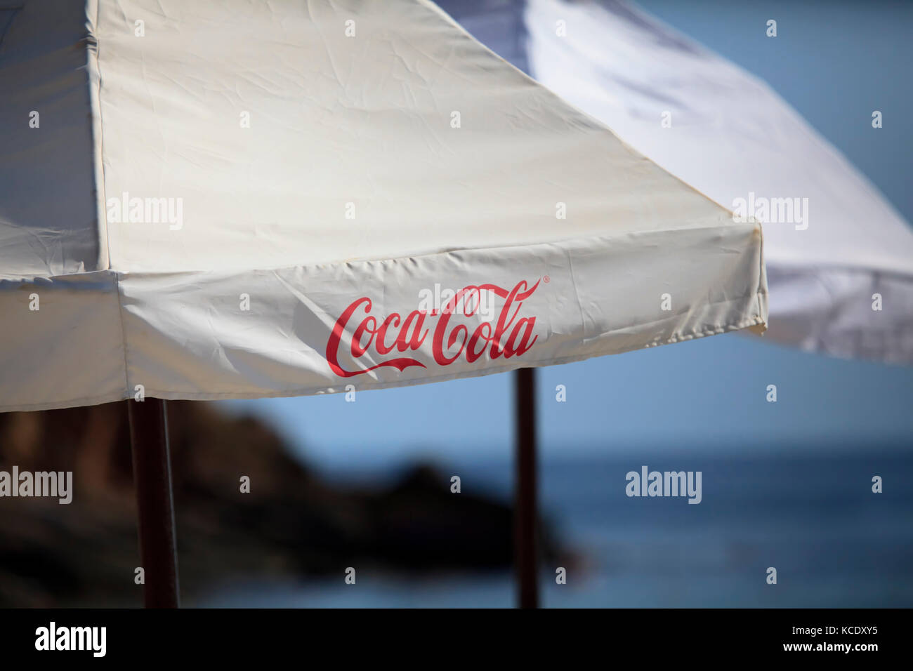SOFIA, BULGARIA - SEPTEMBER 24, 2017: Coca-Cola text on umbrela near sea beach. Coca-cola is the world's most - Stock Image