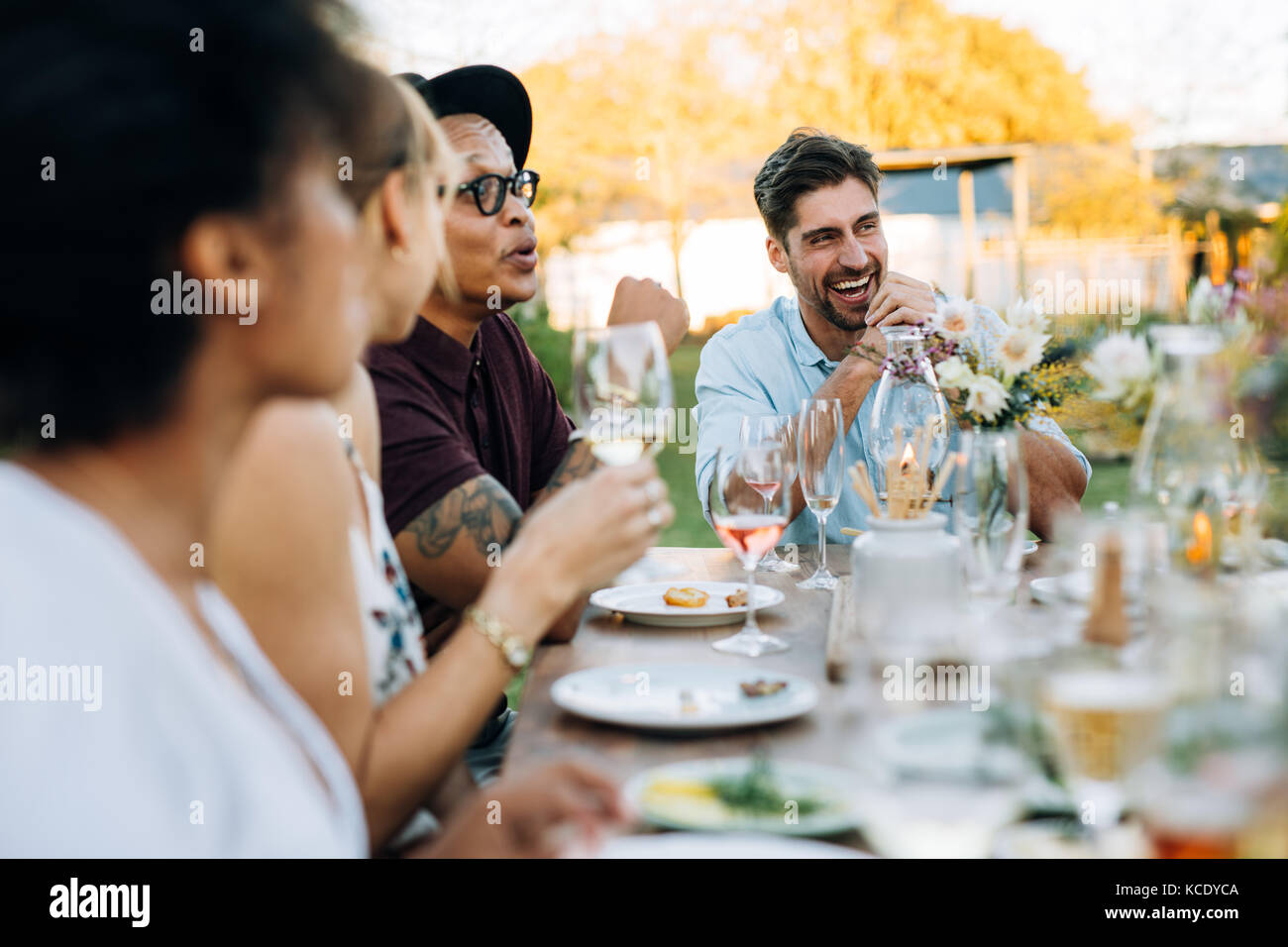 Young man laughing while sitting with friends at outdoors party. Friends enjoying summer meal at outdoor restaurant. - Stock Image