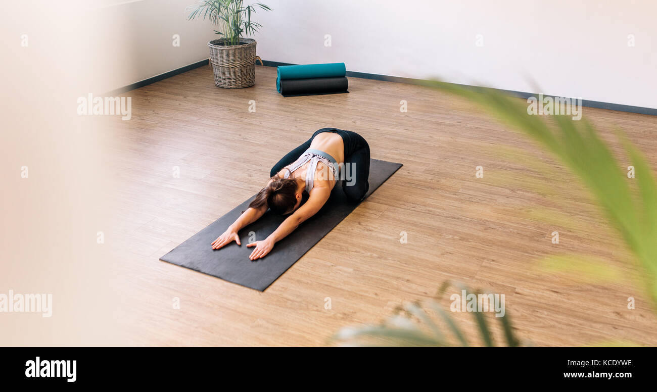 High angle view of healthy woman exercising on yoga mat indoors. Fit female performing child yoga pose at gym class. - Stock Image
