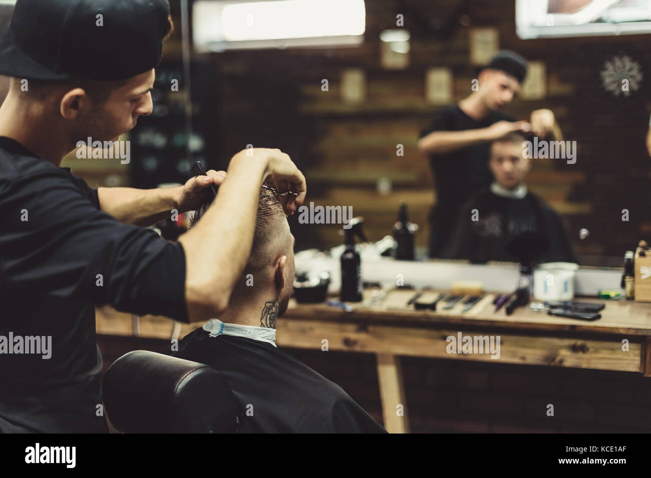 Crop barber doing haircut for client - Stock Image