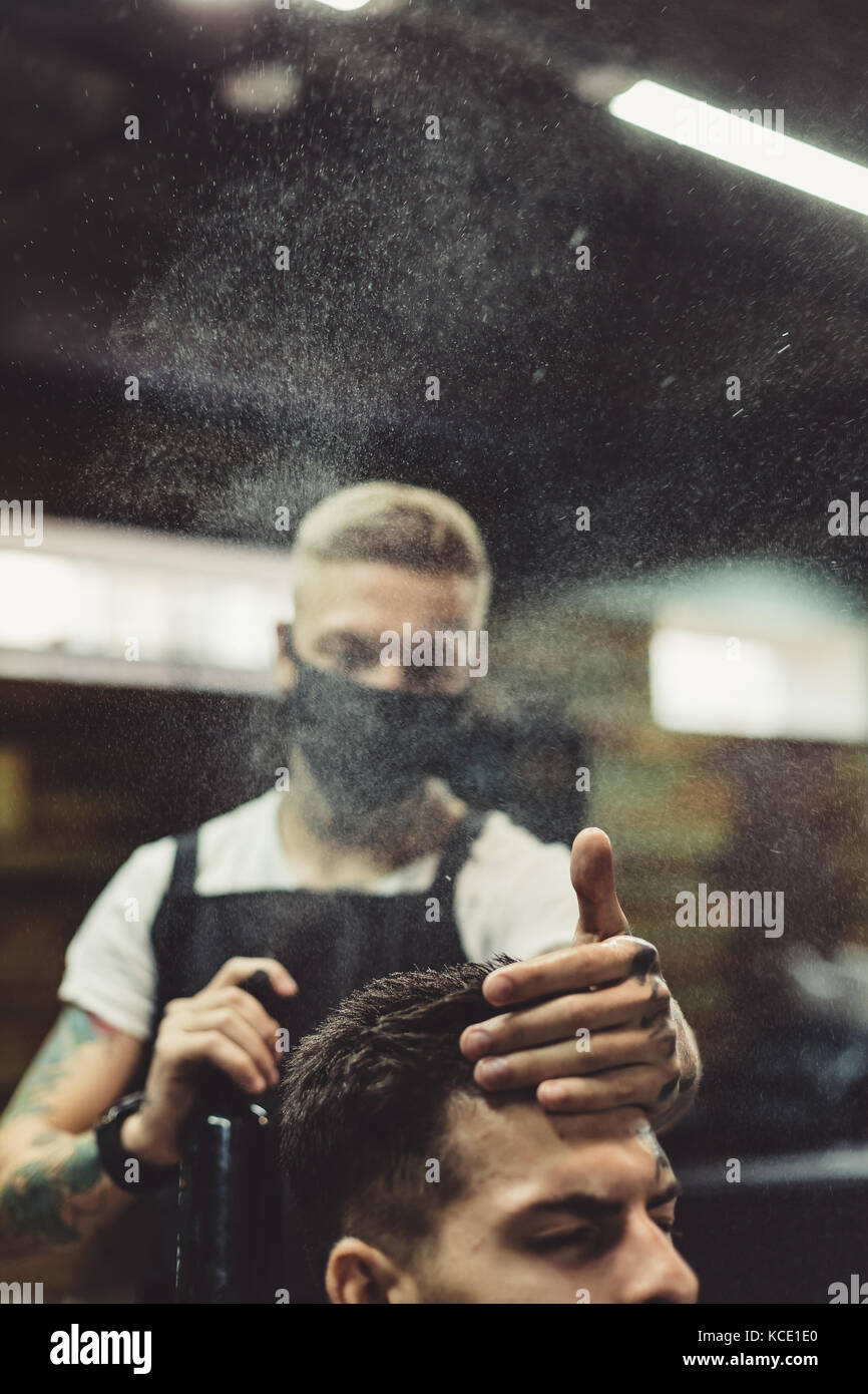 Stylist grooming client in barbershop - Stock Image