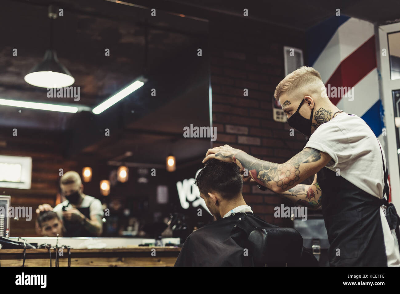 Barber shaving man in chair - Stock Image