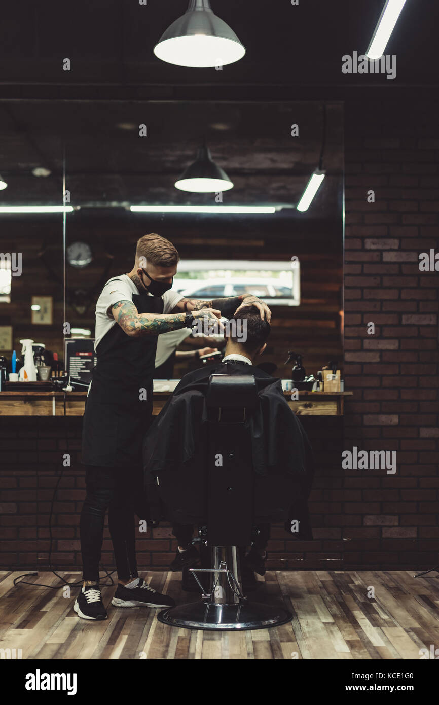 Stylish man working with client in salon - Stock Image