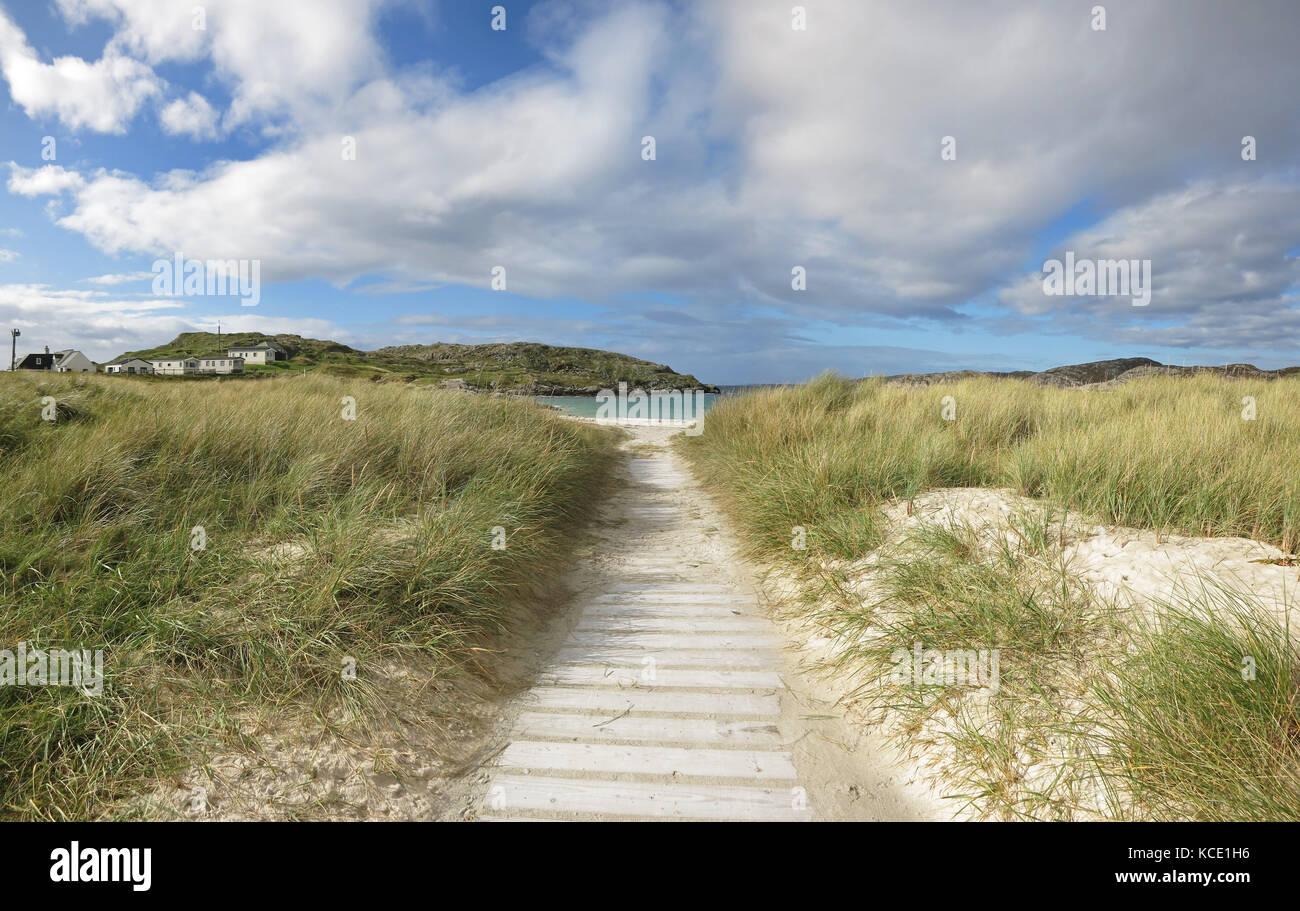 Boarded path through white sand dunes to Achmelvich Beach, near Lochinver, Scotland. - Stock Image